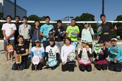 写真:ネットの前でビーチテニス集合写真